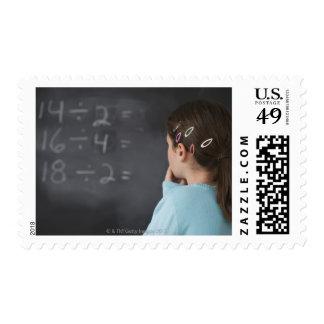 Chica que mira ecuaciones de la matemáticas en la franqueo