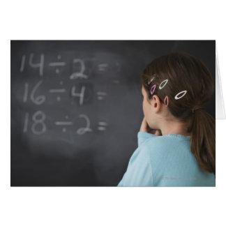 Chica que mira ecuaciones de la matemáticas en la  tarjetón