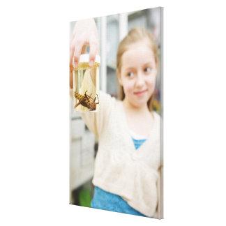 Chica que mira el insecto en tarro en sala de clas lona envuelta para galerias