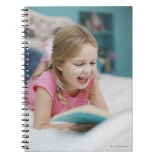 Chica que pone en libro de lectura de la cama cuadernos