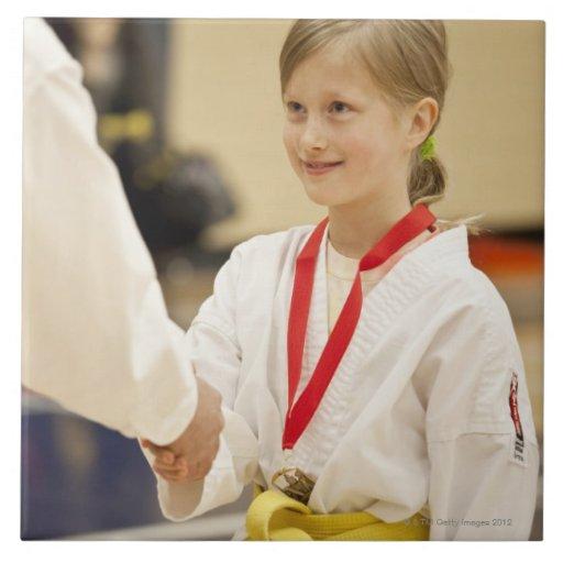 Chica que recibe una medalla en un campeonato del  azulejos