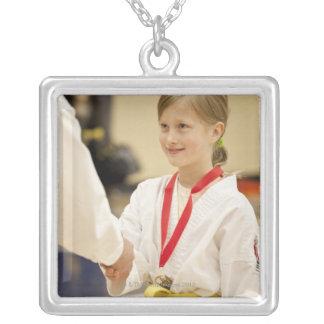 Chica que recibe una medalla en un campeonato del colgante cuadrado