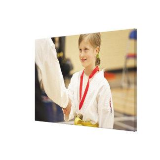 Chica que recibe una medalla en un campeonato del lienzo envuelto para galerias