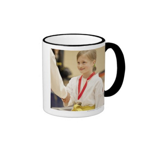Chica que recibe una medalla en un campeonato del  taza de café