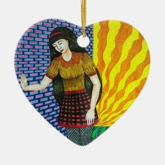 Chica que se inclina en la pared de ladrillo en el adorno navideño de cerámica en forma de corazón
