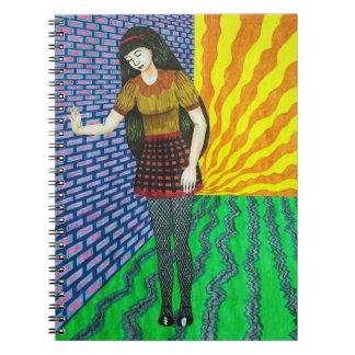 Chica que se inclina en la pared de ladrillo en el libros de apuntes