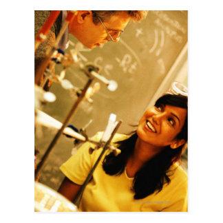 Chica que sonríe en el profesor en laboratorio de postales