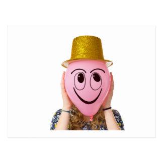 Chica que sostiene el globo con la cara y el gorra postal