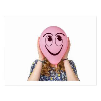 Chica que sostiene el globo rosado con la cara postales