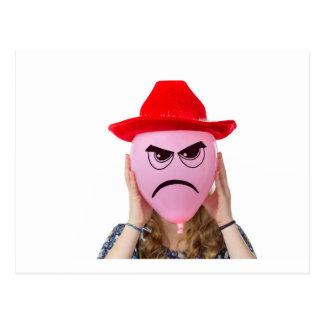 Chica que sostiene el globo rosado con la cara y postales
