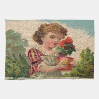 Chica que sostiene un florero de flores toalla de cocina