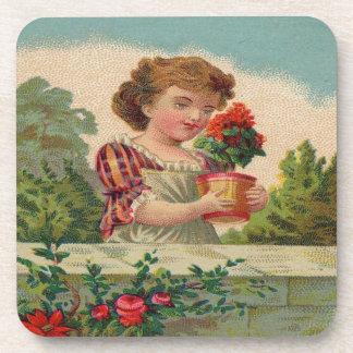 Chica que sostiene un florero de flores posavaso