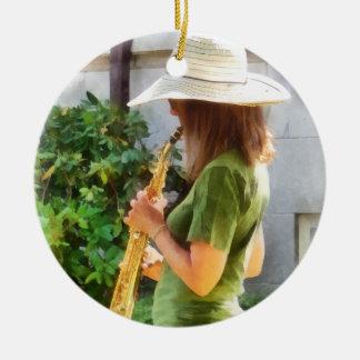 Chica que toca el saxofón adorno redondo de cerámica
