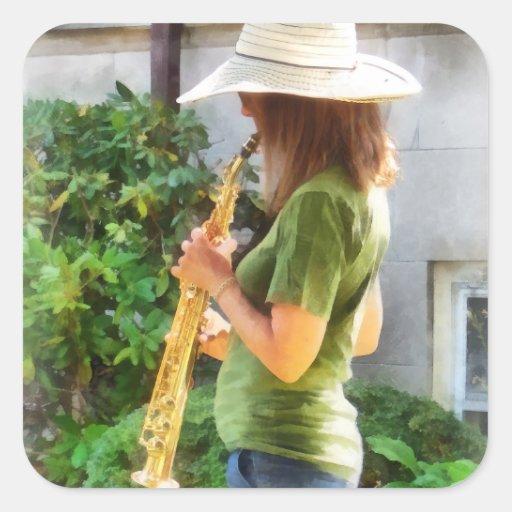 Chica que toca el saxofón pegatina cuadrada