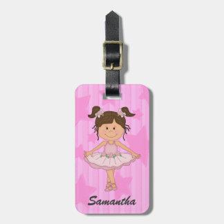 Chica rosado lindo del ballet en las barras y estr etiqueta de equipaje