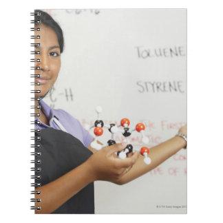 Chica teenaged hispánico en clase de la ciencia libreta