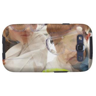 Chica y muchacho (11-13) que miran la placa de Pet Samsung Galaxy SIII Funda