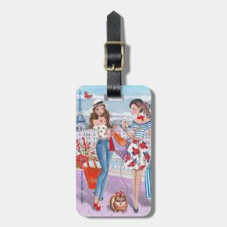 Chicas de compras en etiqueta del equipaje de etiqueta para maleta