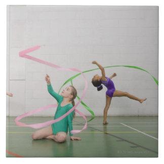 Chicas de la gimnasia que bailan con las cintas azulejo cuadrado grande