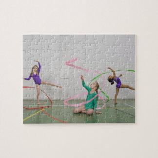 Chicas de la gimnasia que bailan con las cintas rompecabezas con fotos