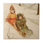 Chicas en un trineo en nieve del invierno azulejos ceramicos