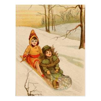 Chicas en un trineo en nieve del invierno postales