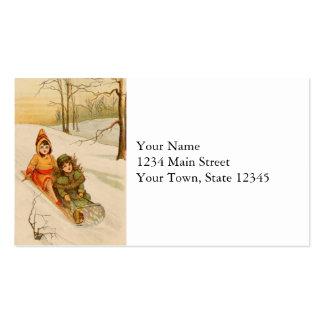 Chicas en un trineo en nieve del invierno tarjetas de visita
