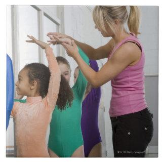 Chicas que estiran en clase de la gimnasia azulejo cuadrado grande