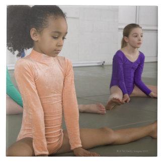 Chicas que estiran en práctica de la gimnasia azulejo cuadrado grande