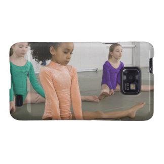 Chicas que estiran en práctica de la gimnasia galaxy SII funda