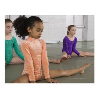 Chicas que estiran en práctica de la gimnasia postales