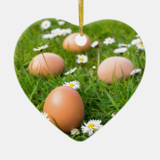 Chicken eggs in spring grass with daisies ceramic ornament