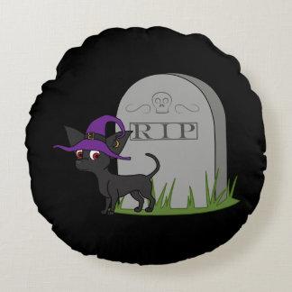 Chihuahua negra con la piedra del sepulcro del cojín redondo