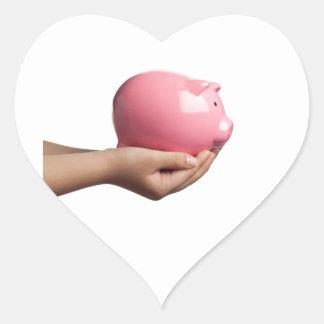 Child holding a piggy bank heart sticker