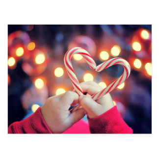 Child holding Christmas candy with heart shape Postcard
