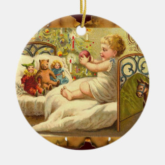 CHILD ON THE BED WITH TOYS AND CHRISTMAS GIFTS CERAMIC ORNAMENT