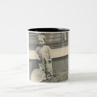 child standing by straw hat mug