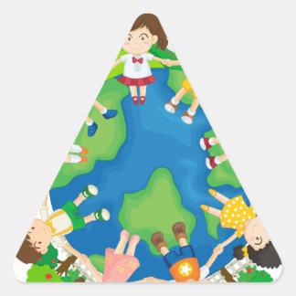 Children holding hands around the earth triangle sticker