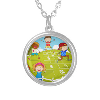 Children playing hopscotch in the park round pendant necklace