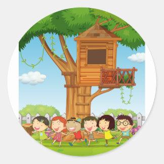 Children playing in the garden classic round sticker