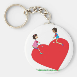 children playing on a heart shaped see-saw keychain