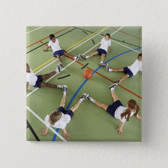 Children sitting on the floor of a sports hall pinback button