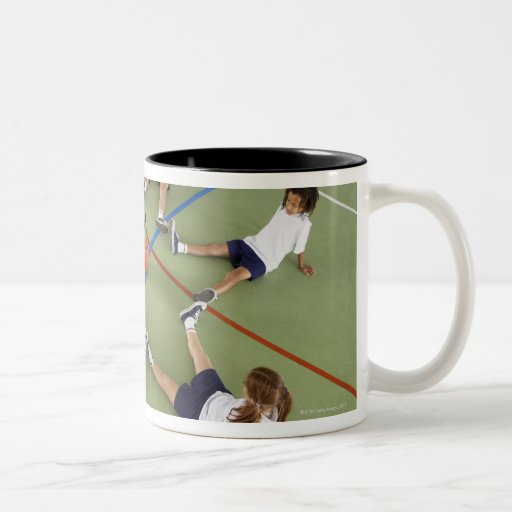 Children sitting on the floor of a sports hall Two-Tone coffee mug