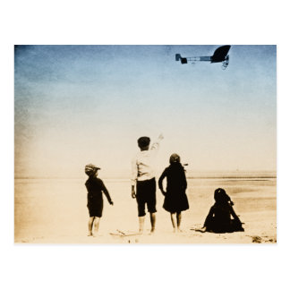 Children watching airplane on the beach postcards