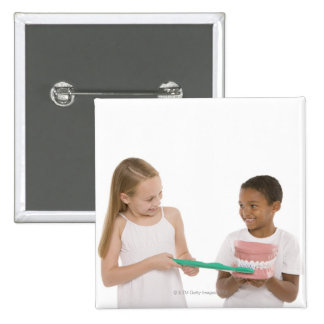 Children with a model set of teeth and oversized 2 inch square button