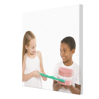 Children with a model set of teeth and oversized canvas print