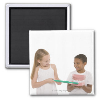 Children with a model set of teeth and oversized 2 inch square magnet