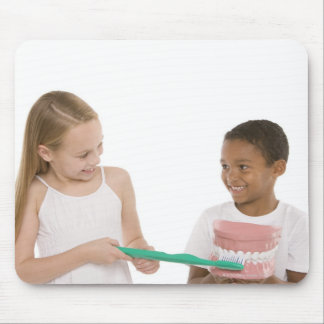 Children with a model set of teeth and oversized mouse pad