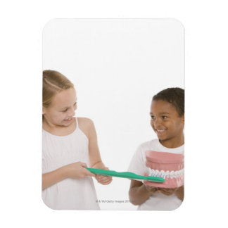 Children with a model set of teeth and oversized rectangular photo magnet