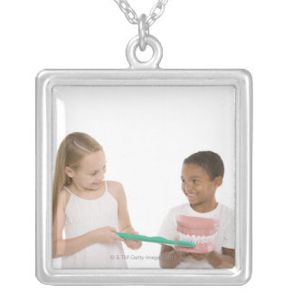 Children with a model set of teeth and oversized silver plated necklace